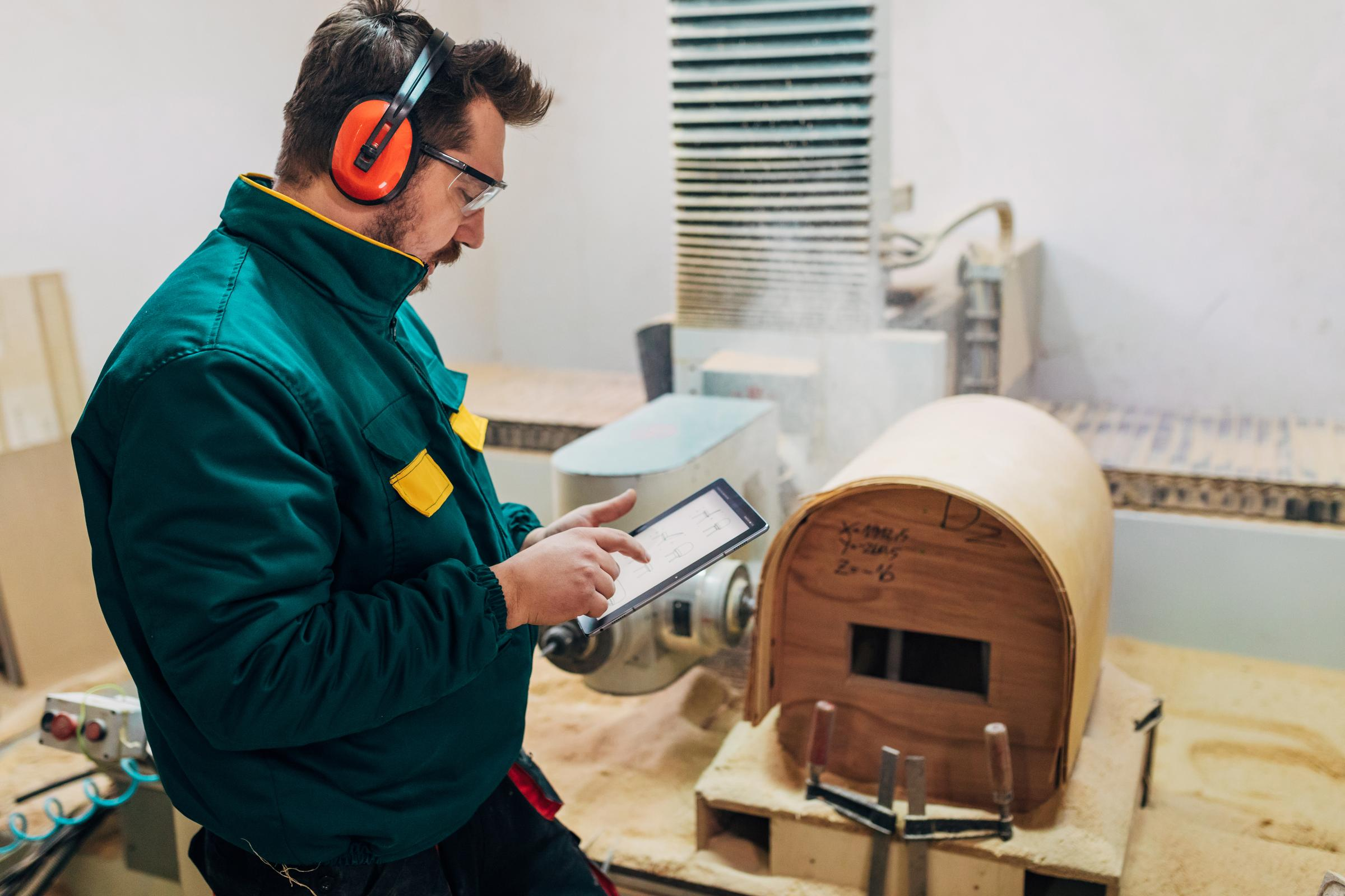 An image shows a man using a table to search for wood working schematics